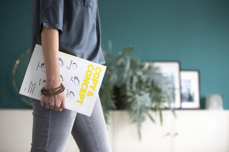 Bedrijfsfotogafie reportage brandingbureau ontwerpbureau vrouw loopt met boek over concepten