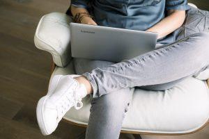 Bedrijfsfotogafie reportage brandingbureau ontwerpbureau vrouw werkt met laptop op schoot