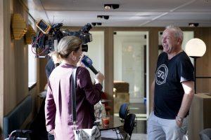 Bedrijfsfotografie voor het Ouderenfonds op Nationale Ouderendag in het Lloyd Hotel in Amsterdam. High Tea met ouderen, Gorden wordt geinterviewd door TV