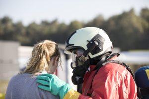 Meisje wordt toegesproken door hulpverlener met gasmasker