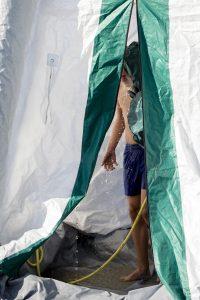 Jongen wordt gedouched in ontsmettingsruimte door hulpverlener met gasmasker