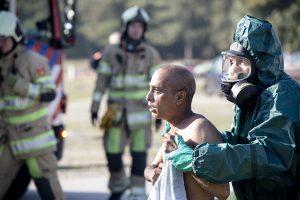 Slachtoffer wordt afgevoerd door hulpverlener met gasmasker
